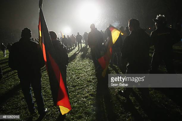 Supporters of the Pegida movement march with German flags at another of their weekly protests on January 5 2015 in Dresden Germany Pegida is an...