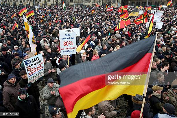 Supporters of the Pegida movement stage protest with banners and German flags at the Theaterplatz Square in Dresden Germany on January 25 2015