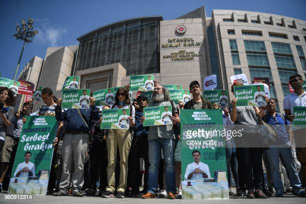 Supporters of the Peoples' Democratic Party hold placards reading 'Free Demirtas' in front of Istanbul's Courthouse on May 21 to demand the release...
