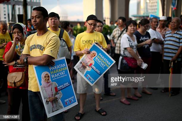 Supporters of the People's Justice Party hold posters of Nurul Izzah daughter of opposition leader Anwar Ibrahim and a member of parliament Lembah...