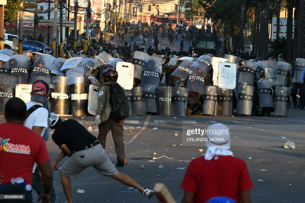Supporters of the presidential candidate for the Honduran Opposition Alliance Against the Dictatorship, Salvador Nasralla, clash with riot police and soldiers in a protest near the presidential palace in Tegucigalpa on January 12, 2018. Thousands of people protested Friday in the Honduran capital against the reelection of President Juan Orlando Hernandez, as the January 27 start of his second term approaches. /