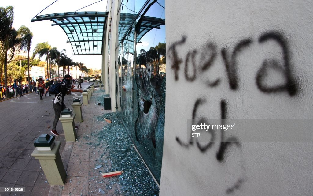 Supporters of the presidential candidate for the Honduran Opposition Alliance Against the Dictatorship, Salvador Nasralla, clash with riot police and soldiers and cause damage to buildings in a protest in Tegucigalpa on January 12, 2018. Thousands of people protested Friday in the Honduran capital against the reelection of President Juan Orlando Hernandez (JOH), as the January 27 start of his second term approaches. /