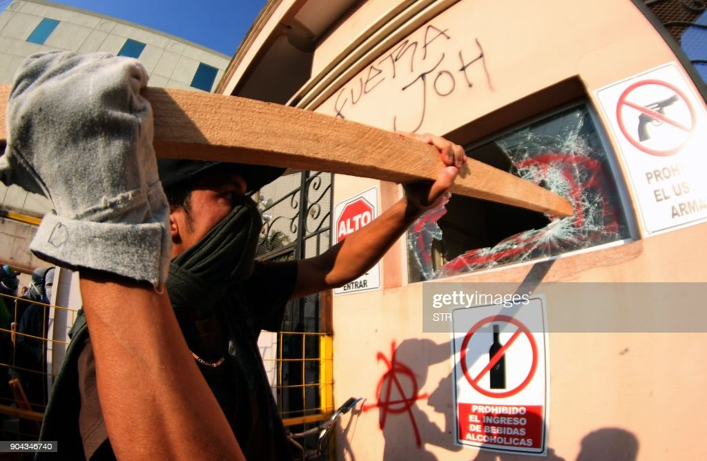 Supporters of the presidential candidate for the Honduran Opposition Alliance Against the Dictatorship, Salvador Nasralla, clash with riot police and soldiers and cause damage to buildings in a protest in Tegucigalpa on January 12, 2018. Thousands of people protested Friday in the Honduran capital against the reelection of President Juan Orlando Hernandez, as the January 27 start of his second term approaches. /