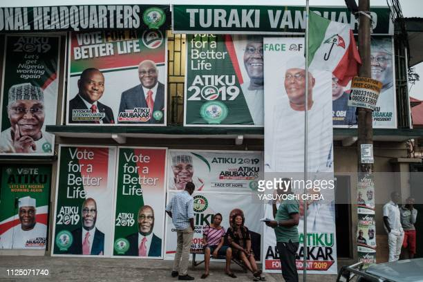Supporters of the presidential candidate of the Nigerian main opposition People Democratic Party Atiku Abubakar sit in front of local campaign office...