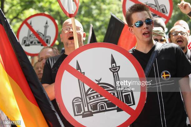 Supporters of the pro Deutschland right-wing anti-Islam group hold up signs showing a mosque with a red line through it outside the Sahaba Salafite...