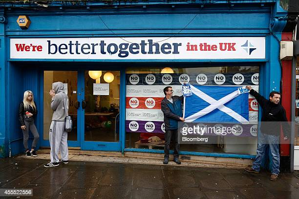 Supporters of the proindependence 'yes' campaign right hold a St Andrew's or Saltire flag the national flag of Scotland as they demonstrate outside...