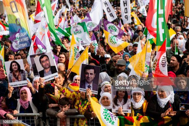 Supporters of the proKurdish Peoples' Democratic Party hold pictures of jailed Kurdish lawmakers as they attend a 'Peace and Justice' rally in...