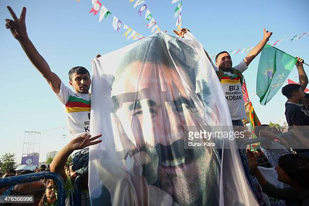 Supporters of the ProKurdish Peoples' Democratic Party wave flags with a picture of the jailed Kurdish militant leader Abdullah Ocalan as they cheer...