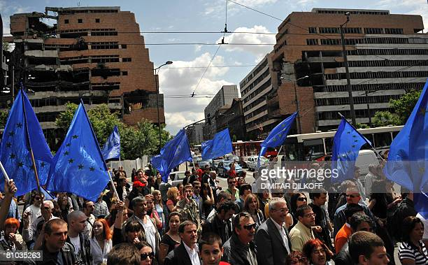 Supporters of the pro-Western Liberal Democratic Party waves EU flags as they pass by buildings destroyed during the NATO bombing in 1999, staging a...
