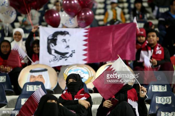 Supporters of the Qatar national football team wave their national flags one of them defaced with the 'Glorious Tamim' painting as they attend the...