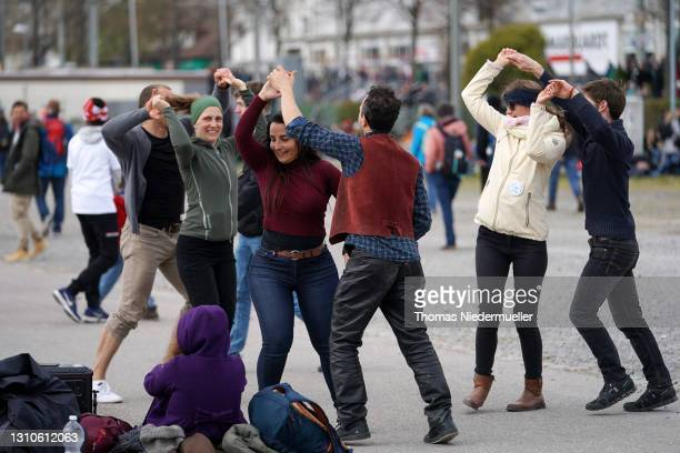 Supporters of the Querdenken movement dance during a rally for what they claim are their basic rights during the third wave of the coronavirus...