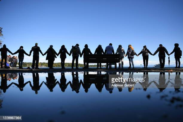 Supporters of the Querdenken movement hold their hands in order to create Europe's biggest ever human chain on October 3 2020 at Konstanz Germany...