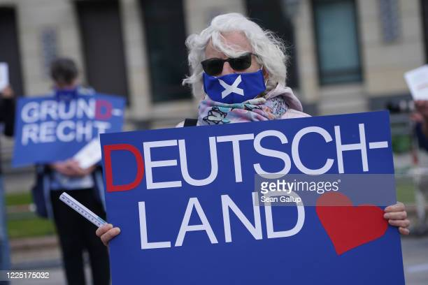 Supporters of the rightwing Alternative for Germany political party wear protective face masks as they hold signs that read basic right and Germany...