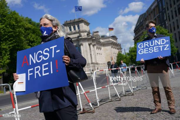 """Supporters of the right-wing Alternative for Germany political party wear protective face masks as they hold signs that read: """"free of fear"""" and..."""