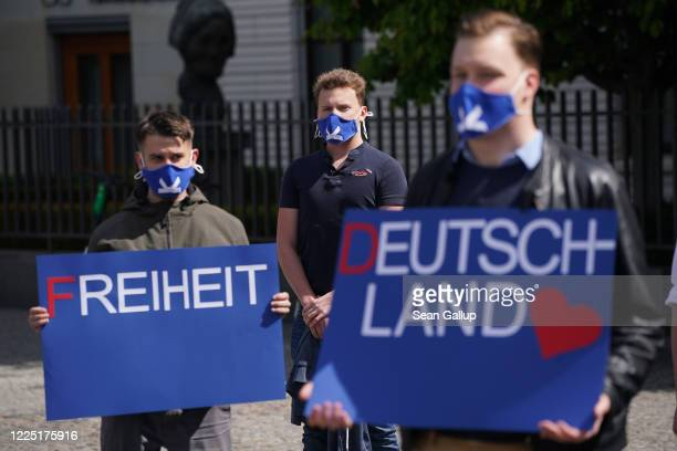 Supporters of the rightwing Alternative for Germany political party wear protective face masks as they hold signs that read freedom and Germany at an...