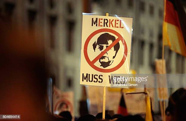 Supporters of the rightwing populist group Pegida holding a placard Merkel muss weg march on January 11 2016 in Munich Germany Pegida and other...