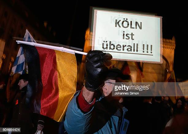 Supporters of the rightwing populist group Pegida holding a placard Koeln ist ueberall march on January 11 2016 in Munich Germany Pegida and other...