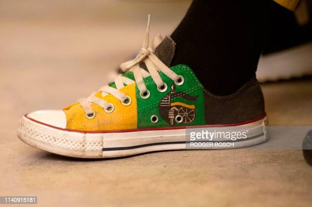 Supporters of the ruling African National Congress wears ANC sneakers during a campaign meeting with the South African president and president of the...