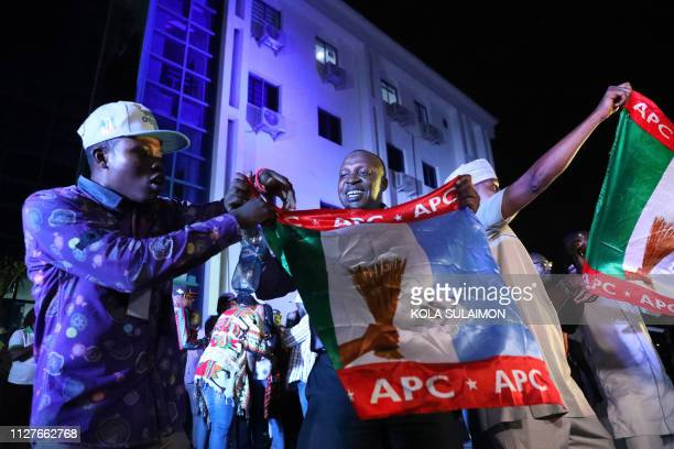 TOPSHOT Supporters of the ruling All Progressives Congress celebrate with party flags in Abuja Nigeria after candidate President Mohammadu Buhari was...