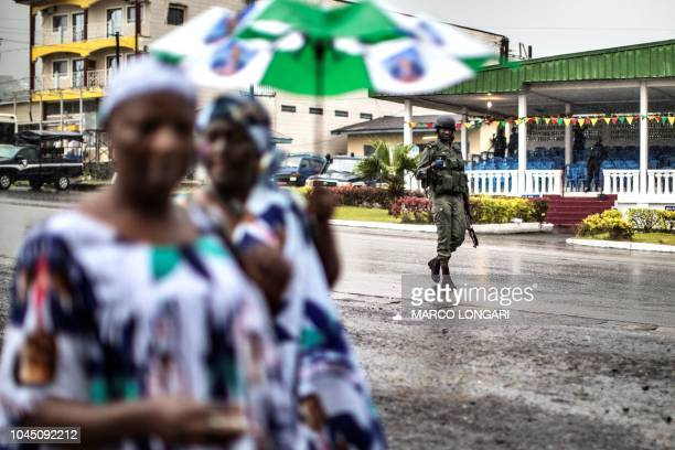 Supporters of the ruling CPDM, Cameroon Pepole's Democratic Movement of incumbent Cameroonian President Paul Biya walk under the watch of a gendarme...