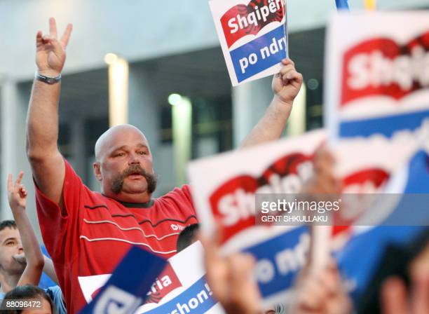 Supporters of the ruling Democratic Party of Albania display placards as unseen Prime Minister and party leader Sali Berisha speaks during the...