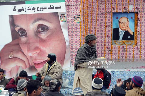 Supporters of the ruling Pakistan Peoples Party distribute communal food past portraits of former premier Benazir Bhutto and her father and former...