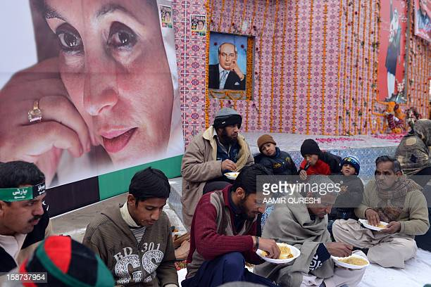 Supporters of the ruling Pakistan Peoples Party eat communal food in front of portraits of former premier Benazir Bhutto and her father and former...
