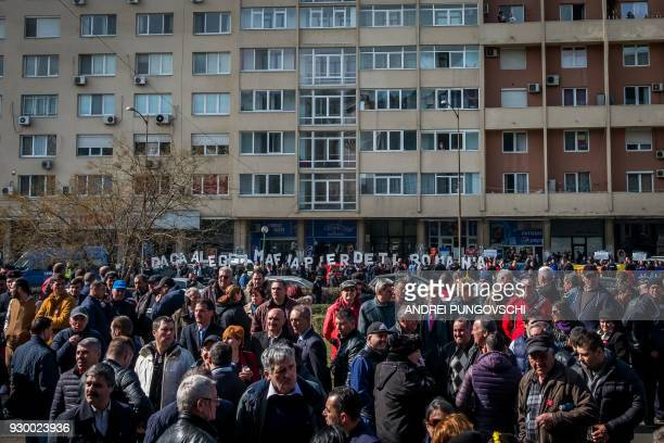 Supporters of the ruling Social Democrat Party stand in front of protesters holding letters to read If you choose the mafia you lose Romania during a...