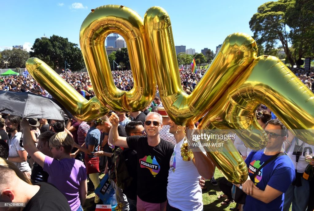 TOPSHOT - Supporters of the same-sex marriage 'Yes' vote gather to celebrate the announcement in a Sydney park on November 15, 2017. Australians voted in favour of allowing same-sex couples to marry, official results showed on November 15, sending the task of legalising marriage equality to a deeply divided parliament. /
