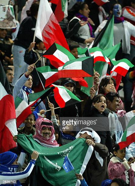 Supporters of the Saudi team holding national and Kuwaiti flags celebrate Saudi Arabia's victory over Bahrain in their Gulf Cup tournament match in...