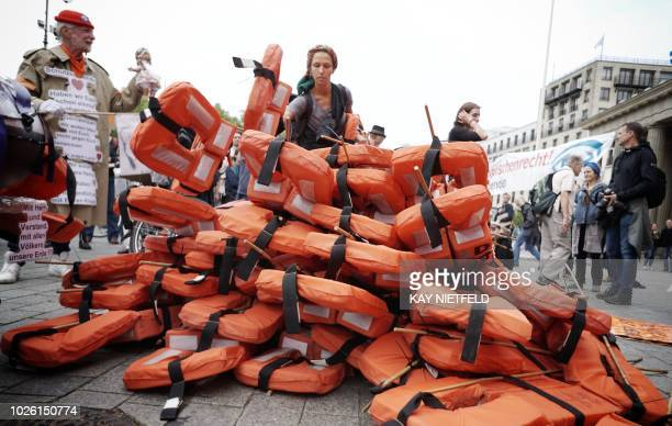 Supporters of the Seebruecke movement pile up life vests during a demonstration for unhampered sea rescue of refugees in the Mediterranean Sea and...