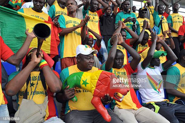 Supporters of the Senegal National football team dubbed the Lions of the Teranga cheer with a plastic lion painted in the country's colours during a...