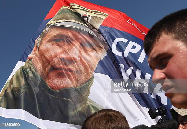Supporters of the Serbian Radical Party stand by a flag that depicts Ratko Mladic former Chief of Staff of the Bosnian Serb army and currently on...