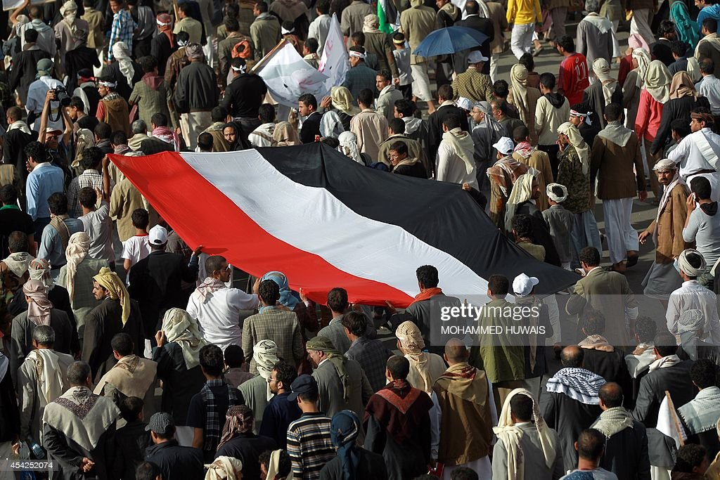 Supporters of the Shiite Huthi movement hold a giant national flag during an anti-government protest on August 27, 2014 in the Yemeni capital Sanaa. Yemeni President Abdrabuh Mansur Hadi urged Shiite rebel leader Abdulmalik al-Huthi on August 26 to withdraw his militant followers from the capital following the failure of negotiations on their demands.