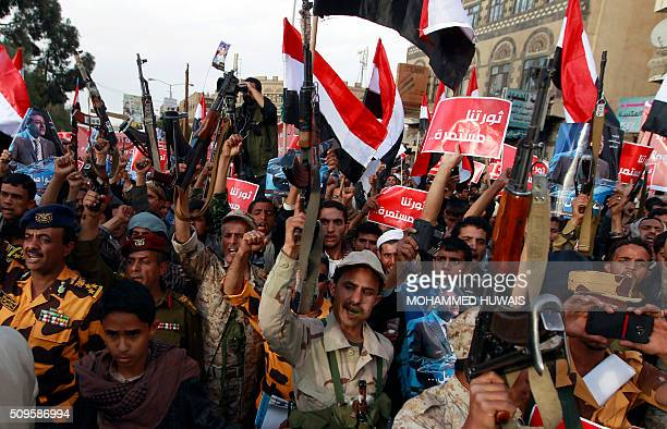 TOPSHOT Supporters of the Shiite Huthi movement wave their national flag and banners reading in Arabic our revolution continues as they shout slogans...