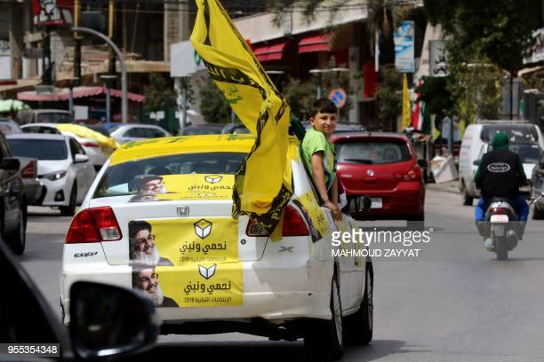 Supporters of the Shiite Muslim Hezbollah movement tour the city of Nabatieh in southern Lebanon on May 6 as the country votes in its first...
