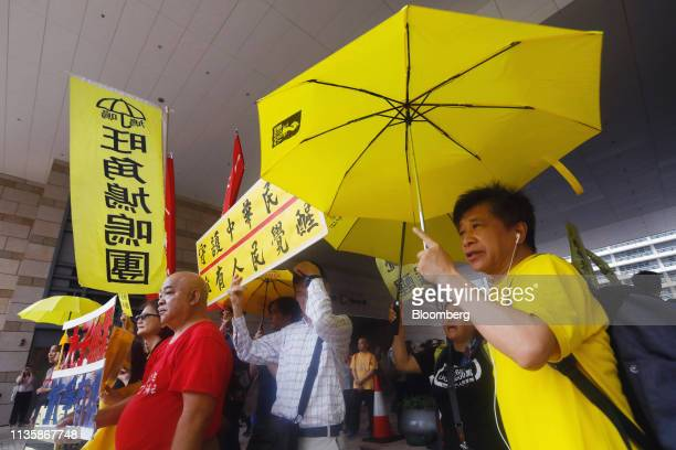Supporters of the socalled Umbrella Nine democracy activists raise yellow umbrellas and placards outside a district court ahead of their verdicts...