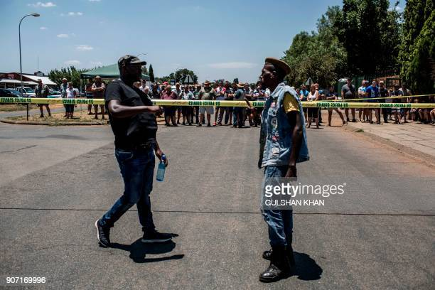 Supporters of the South African ruling party African National congress protest against the language and admission policies outside the Horskool...