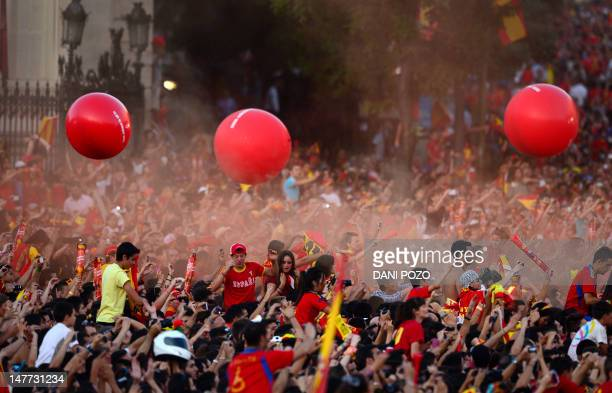 Supporters of the Spanish national football team celebrate on July 2 2012 on Cibeles Square in Madrid a day after it won the final match of the Euro...