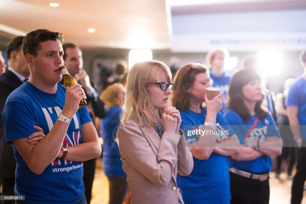 Supporters of the 'Stronger In' Campaign watch the results of the EU referendum being announced at a results party at the Royal Festival Hall in London on June 24, 2016. Britain's economy was plunged into a dizzying unknown on Friday as the country lurched towards the EU exit, with the world economy bracing for a hit on growth and unemployment. /