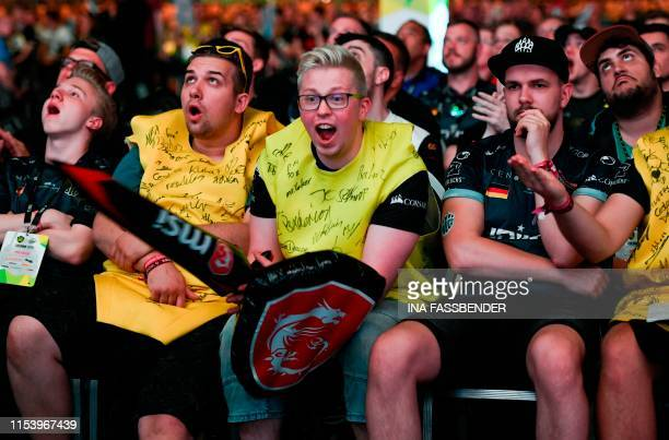 Supporters of the teams 'NAVIGGBET' and 'Ninjas in pyjamas' react during the ESL ONE CounterStrike video game tournament at the Lanxess Arena in...