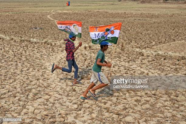 Supporters of the Trinamool Congress party carry the party flag as they cross a paddy field to attend a public meeting held by Chief Minister of West...