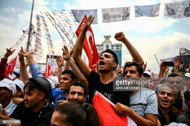 TOPSHOT Supporters of the Turkish President shout slogans as they attend a campaign rally in Istanbul on June 23 one day before presidential and...