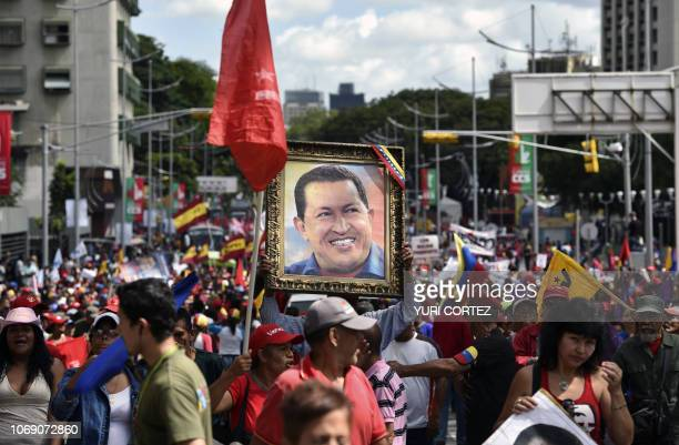 Supporters of the United Socialist Party of Venezuela carry a portrait of late Venezuelan president Hugo Chavez during a rally to commemorate the...