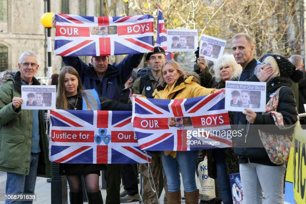 Supporters of the victims are seen with flags outside the Royal Courts Of Justice London Supporters of Josh Kennedy aged 16 Harry Rice aged 17 and...