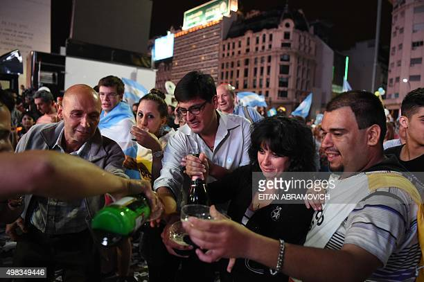 Supporters of the victorious presidential hopeful of the Cambiemos party Mauricio Macri celebrate his win over leftist Daniel Scioli at Buenos Aires'...
