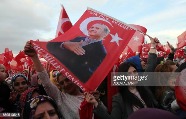 Supporters of the 'yes' wave Turkish National flags and flags depicting Turkish president Recep Tayyip Erdogan as they cheer during his speech at the...
