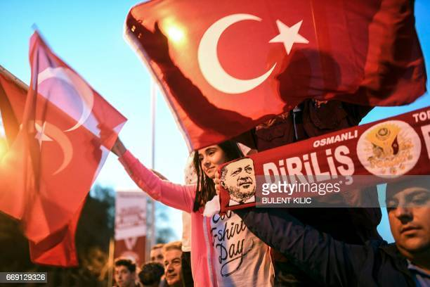 Supporters of the 'yes' wave Turkish national flags and scarfs picturing Turkish president Recep Tayyip Erdogan during a rally in front of the...