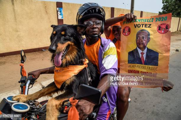 Supporters of Togo's major opposition candidate of the National Alliance for Change party Jean-Pierre Fabre ride with a dog on a motorcycle during...