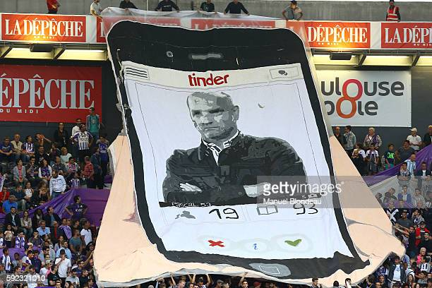 Supporters of Toulouse FC hold up a giant banner display the face of the head coach Pascal Dupraz during the Ligue 1 match between Toulouse Fc and...